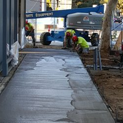An image of sidewalk concrete being poured